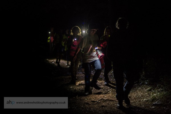 Torches guide the way through the pitch dark woods